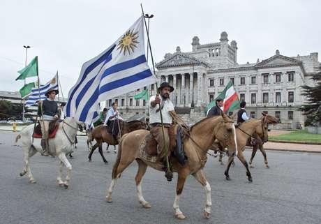 Homens a cavalo levam bandeira do Uruguai perto do Congresso do país em Montevidéu 16/04/2002 REUTERS/Andres Stapff