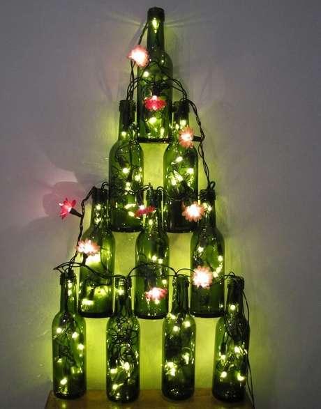 57. Árvore de Natal na parede feita com garrafas de vidro e pisca pisca. Fonte: Casa e Festa