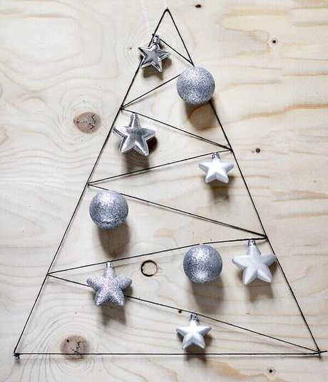 68. Árvore de Natal na parede feita com aramado e enfeites natalinos. Fonte: Pinterest