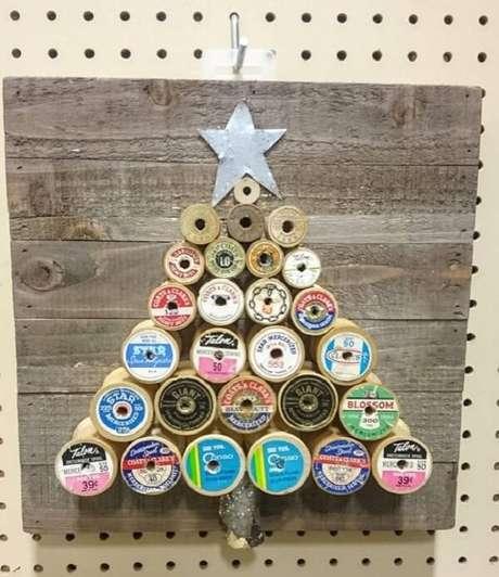 70. Árvore de Natal na parede feita com carretéis de linhas. Fonte: Etsy
