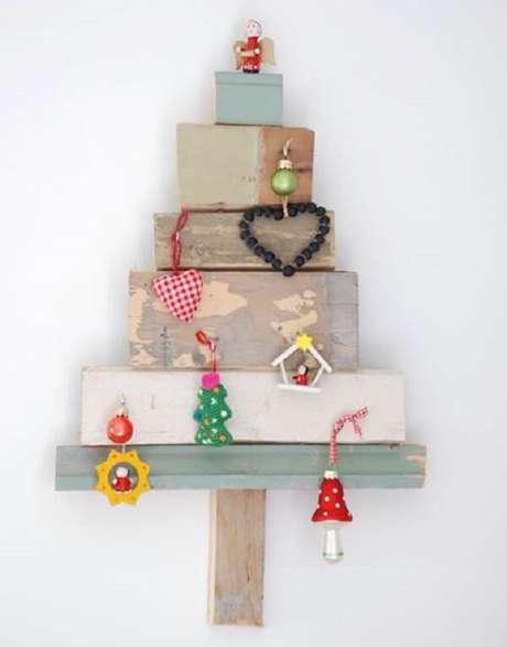 40. Tocos de madeira e enfeites formam a árvore de Natal na parede. Fonte: Pinterest