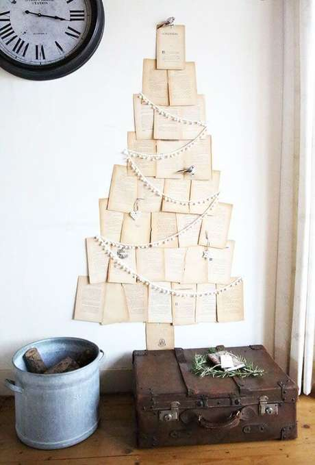 41. Utilize folhas de livro ou revista para estruturar sua árvore de Natal na parede. Fonte: Pinterest