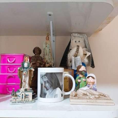 Objetos temáticos estão espalhados pela casa de Milena, que diz ter escapado da morte após intercessão da freira
