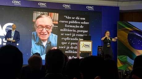 Eduardo Bolsonaro fala no palco, com imagem e frase de Olavo de Carvalho na tela atrás; em primeira edição de evento conservador no Brasil, o deputado foi ovacionado pela plateia