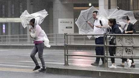 Pedestres têm dificuldade para caminhar por causa de chuva e vento fortes