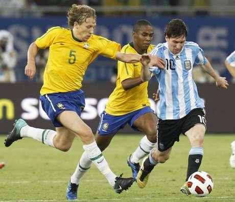 Lionel Messi dribla jogadores brasileiros em confronto entre Argentina e Brasil, em Doha, no Catar (17/11/2010)