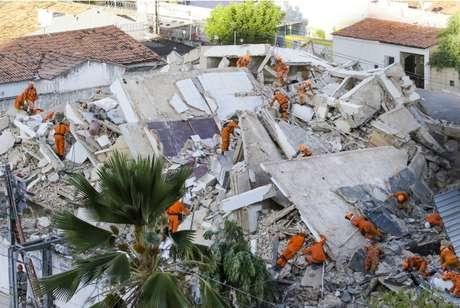 Agentes do Corpo de Bombeiros do Ceará trabalhando nos escombros do prédio que desabou na manhã desta terça-feira.