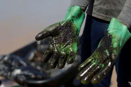Trabalho de limpeza de manchas de óleo na praia de Coruripe, Alagoas 14/10/2019 REUTERS/Adriano Machado