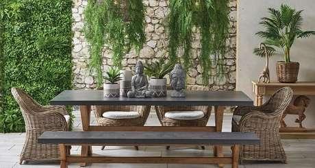 23. Varanda espaçosa com parede de pedra, vasos suspensos e jardim vertical com plantas artificiais. Fonte: Flora Belle