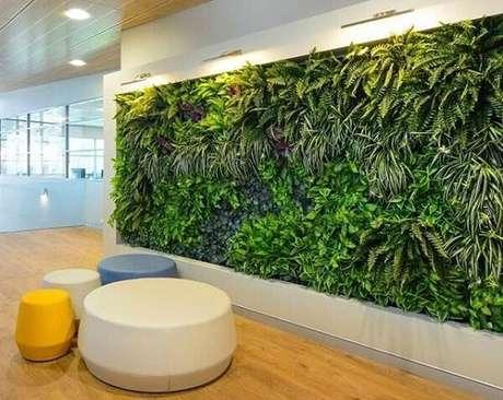 25. Escritório com parede revestida por um jardim vertical artificial traz aconchego aos funcionários. Fonte: Pinterest