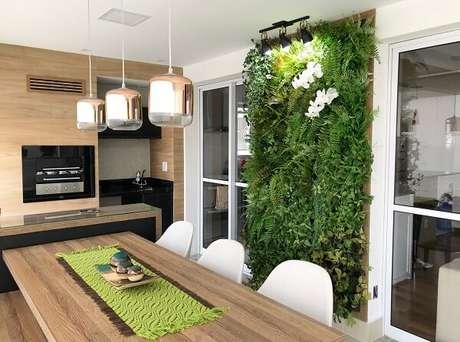 58. Varanda com mesa de madeira e jardim vertical com flores artificiais. Fonte: Art Lilac