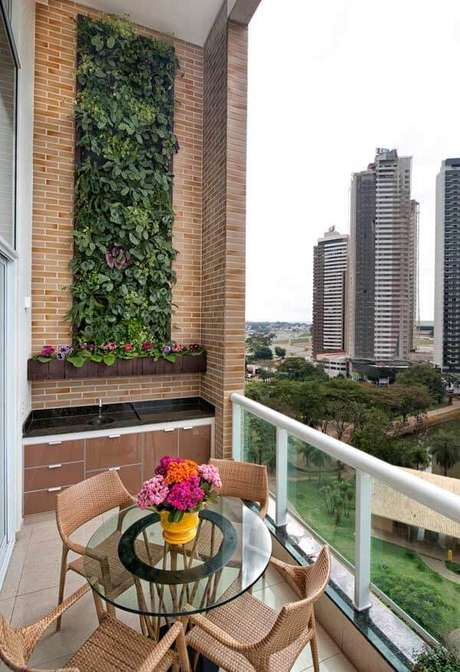 51. Varanda com pé direto alto e parede revestida com jardim vertical artificial. Fonte: Ideias Decor