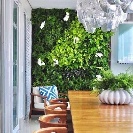 1. Sala de jantar com móveis de madeira e parede revestida com jardim vertical artificial. Fonte: Pinterest