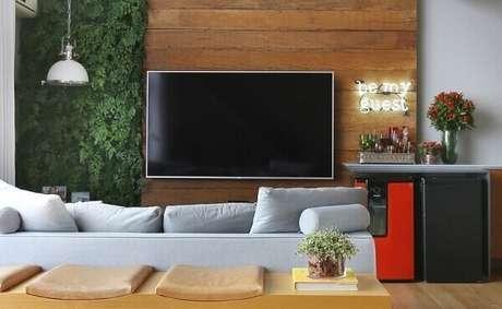 37. O jardim vertical com flores artificiais decora o ambiente da sala de estar. Fonte: Pinterest