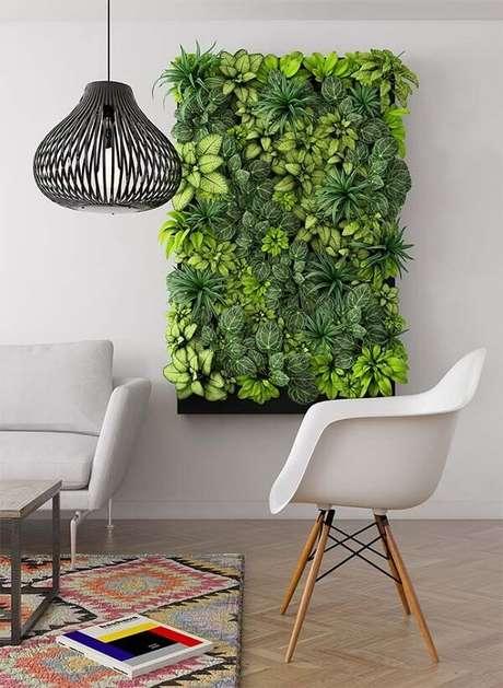 42. O tom verde do jardim vertical artificial traz alegria para a decoração da sala de estar. Fonte: Pinterest