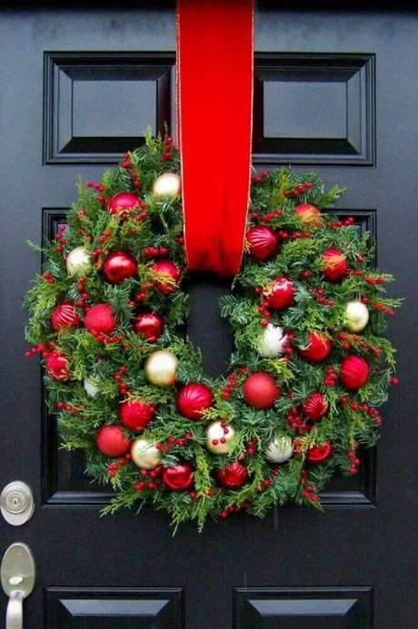 103. Os modelos tradicionais de guirlandas natalinas dão um toque super especial à decoração da frente da casa. Foto: Pinterest