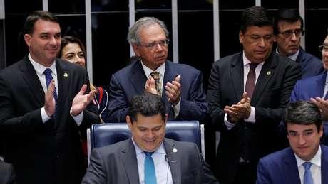 O senador Flávio Bolsonaro, o ministro Paulo Guedes (na foto, os dois à esquerda e em pé) e o presidente da Casa, Davi Alcolumbre (sentado, ao centro), entre outros, comemoram aprovação de texto-base no Senado