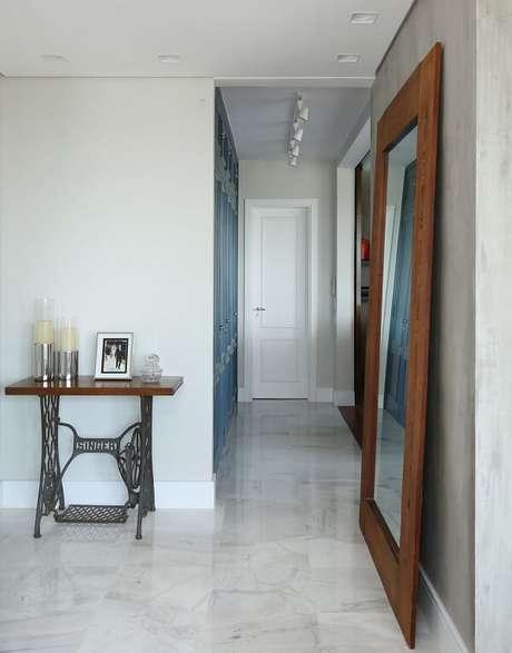 14. Ambiente com parede de cimento queimado e espelho grande. Projeto por Lucia Wjuniski