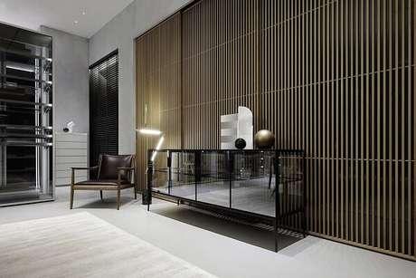 15. Ambiente decorado com aparador, cadeira de couro e parede de cimento queimado. Fonte: Revista Viva Decora