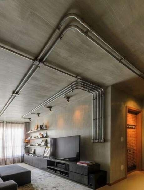 16. Ambiente decorado com elétrica aparente e parede de cimento queimado. Fonte: Revista Viva Decora