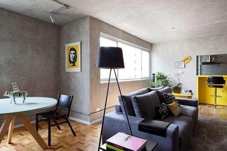 5. Ambiente integrado com luminária de piso e parede de cimento queimado. Projeto por Suite Arquitetos