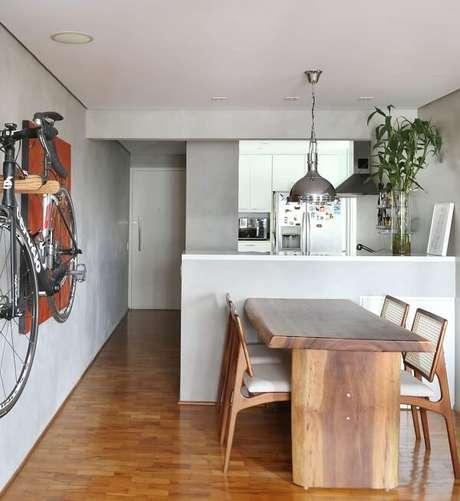 18. Apartamento decorado com mesa de madeira e parede de cimento queimado. Projeto por Oliveira Arquitetura
