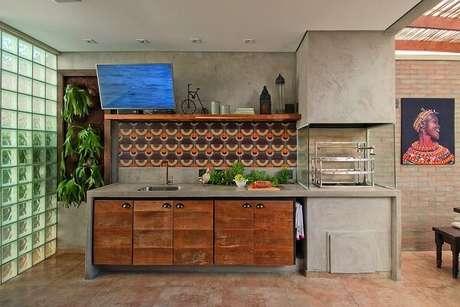 19. Área gourmet com churrasqueira de vidro e parede de cimento queimado. Fonte: Revista Viva Decora