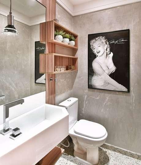 21. Banheiro com piso de granito claro e parede de cimento queimado. Projeto por Tetriz Arquitetura e Interiores
