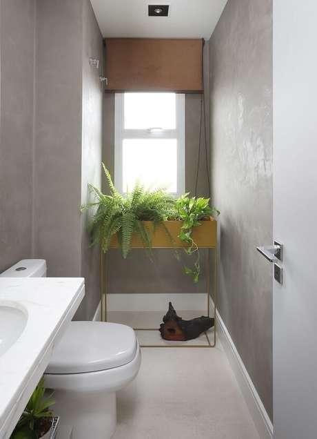22. Banheiro compacto com parede de cimento queimado e bancada de granito. Projeto por Inside Arquitetura e Design