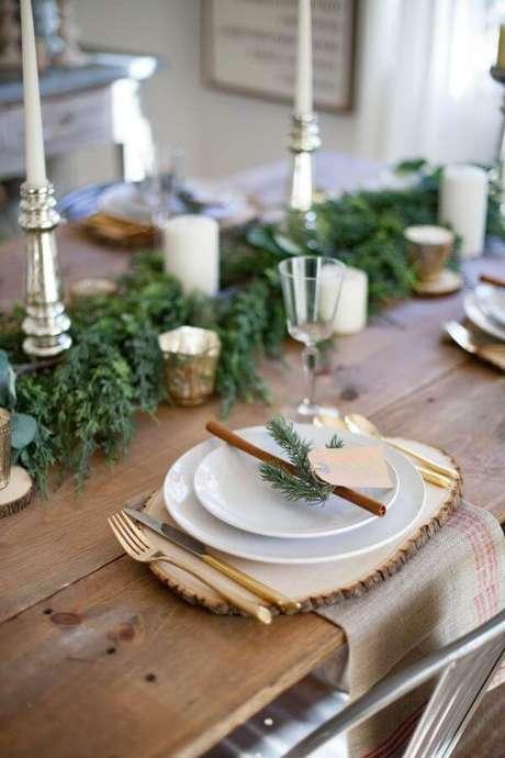 21. Decoração de mesa de natal simples com plantas e castiçais prateadas – Por: The Spruce