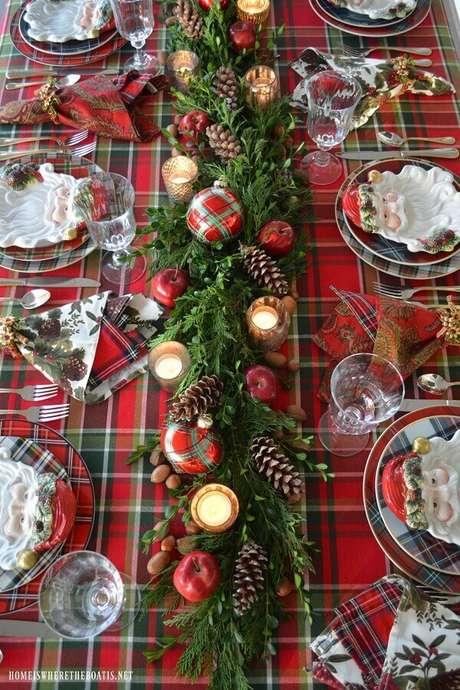 32. A toalha xadrez junto com um lindo arranjo com pinhas e velas pode garantir uma decoração de mesa natalina especial – Foto: Pinterest