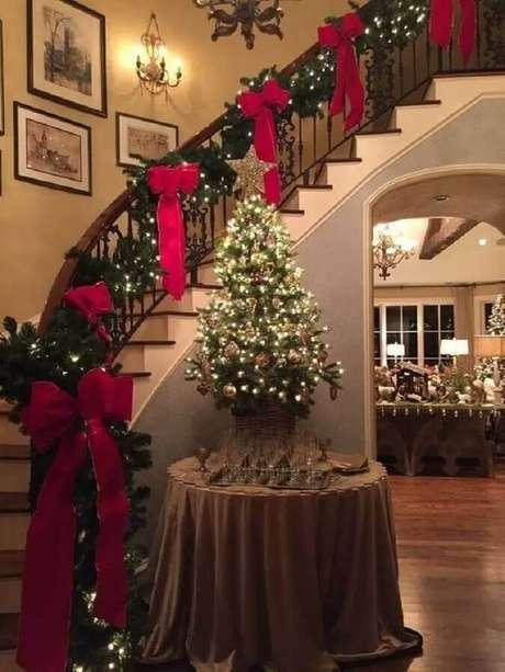 43. Decoração natalina para casas clássicas com laços vermelhos e pisca pisca na escada – Foto: Top Interiors Design