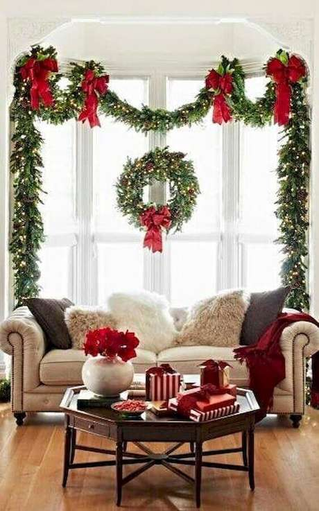 63. Decoração de Natal clássica para sala com guirlanda e laços vermelhos – Foto: Houses Idea