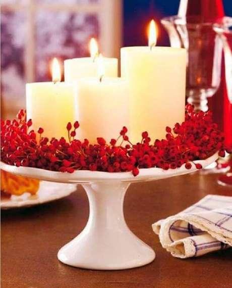 65. Decoração natalina simples com arranjo de velas e plantinhas vermelhas – Foto: Vera Moraes