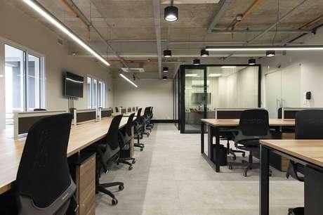 32. Escritório com cadeiras pretas, bancada de madeira e parede de cimento queimado. Projeto por Gabriela Toledo Arquitetura e Interiores