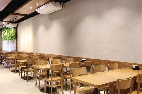 33. Estabelecimento comercial com parede de cimento queimado e móveis de madeira. Projeto por CGAU Arquitetura
