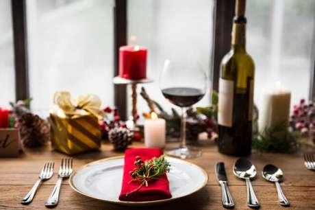 3. Mesa de natal com guardanapo vermelho, taça de vinho e velas – Por: Freepik