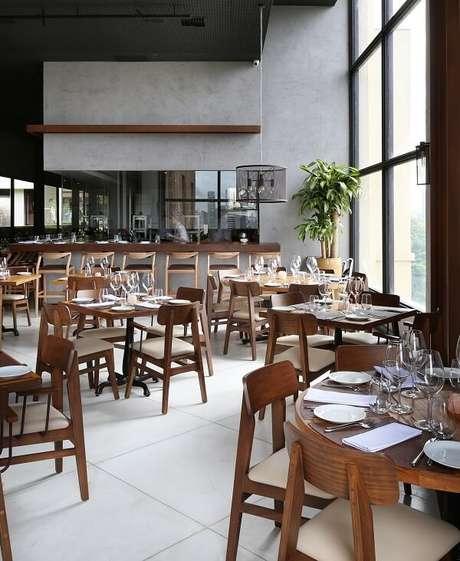 49. Restaurante com móveis de madeira e parede de cimento queimado. Projeto por CG Arquitetura