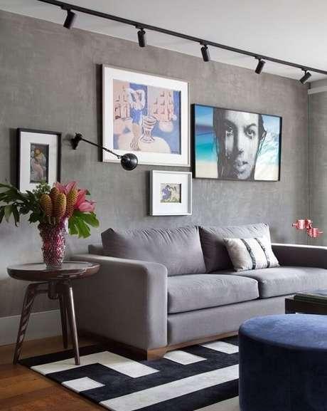 70. Sala de estar com iluminação em trilhos e parede de cimento queimado. Fonte: Pinterest