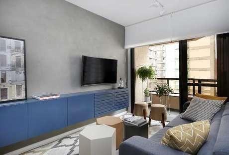 50. Sala de estar com rack azul e parede de cimento queimado. Projeto por ACF Arquitetura