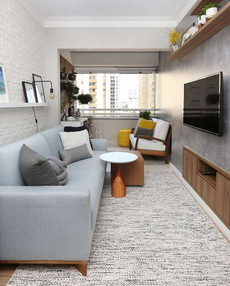 52. Sala de estar compacta com parede de cimento queimado e sofá azul bebê. Projeto por Livia Dalmaso