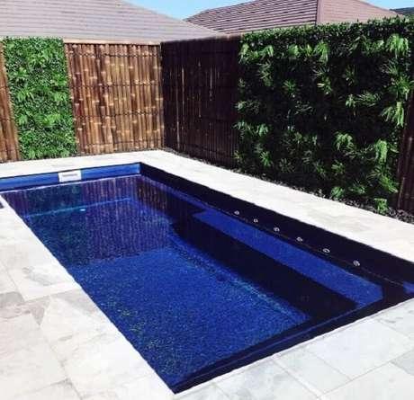 77. O jardim vertical e a cerca encantam a decoração da piscina. Fonte: Pinterest