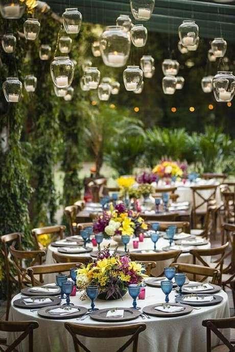 64. Decoração de casamento no campo com velas suspensas e arranjos de flores nas mesas dos convidados – Foto: Luxury Wedding