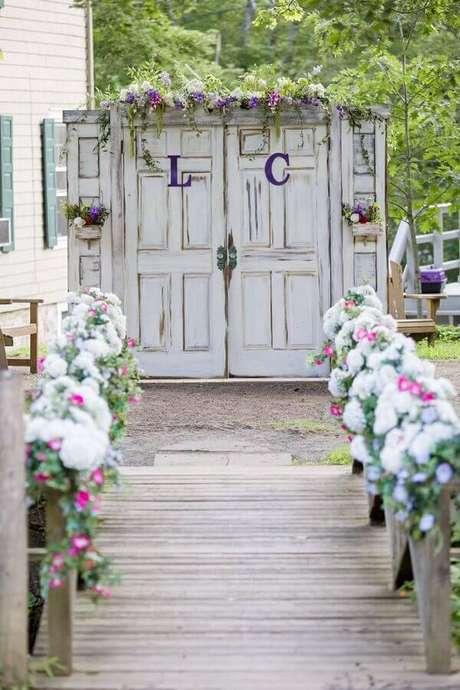 40. Decoração rústica para cerimônia de casamento no campo com porta antiga e arranjo de flores – Foto: Pinterest