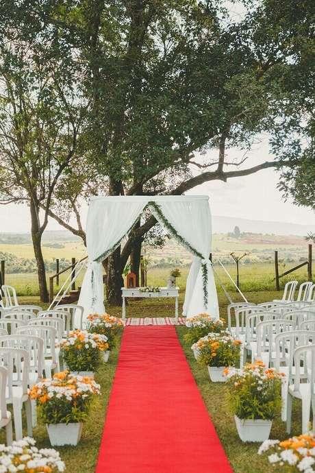 48. Decoração para casamento simples no campo com tapete vermelho e arranjo de flores do campo – Foto: Pinterest