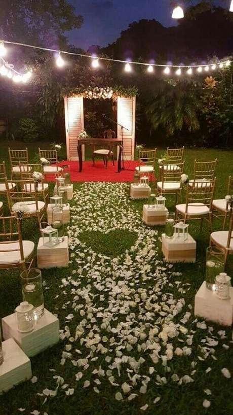 38. Caminho com pétalas de flores brancas para cerimônia de casamento no campo a noite – Foto: Pinterest