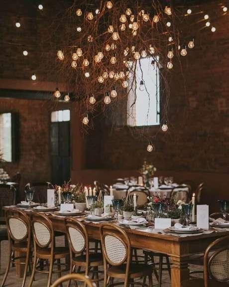 46. Decoração para casamento rústico no campo com galhos secos e lâmpadas – Foto: Estúdio Pinus