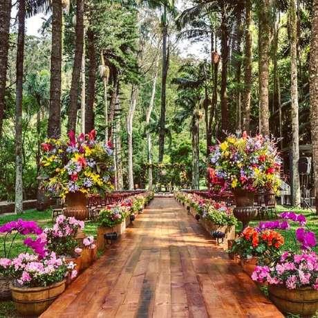53. Linda decoração com vários arranjos de flores coloridas para cerimônia de casamento no campo – Foto: MBacellar Festas