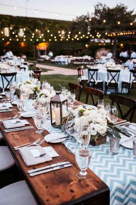 34. Decoração com arranjo de flores brancas e luminárias com velas para festa de casamento no campo – Foto: Blog Meu Casamento