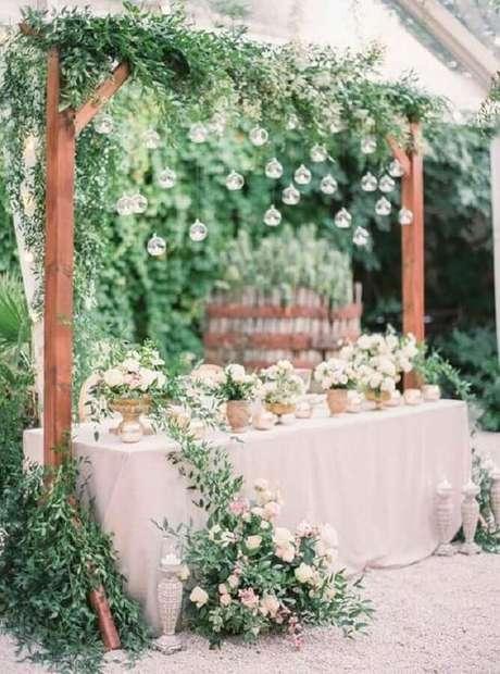63. Mesa de festa de casamento no campo decorada com muita folhagem e lâmpadas – Foto: Etsy